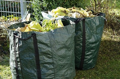 Large reusable rubbish bags full of green waste